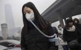 cinesi con la mascherina per lo smog