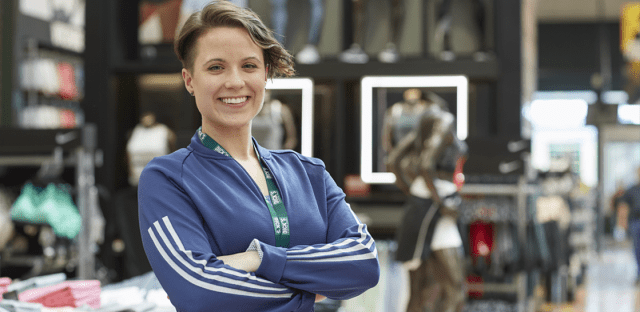 Woman Smiling Wearing Blue Long Sleeved Shirt In Dicks Sporting Goods Retail Store