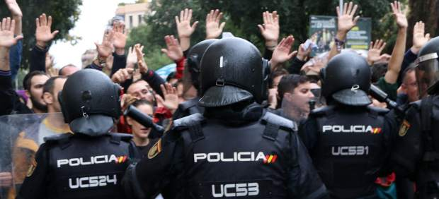 Observadores internacionales delante de un hombre con una herida en la cabeza después de las intervenciones policiales en el CEIP Ramon Llull (Barcelona).