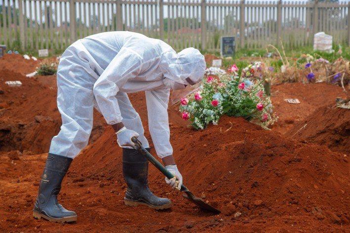 A man, dressed in protective clothing, works at a grave in Vlakfontein Cemetery on 8 January 2021.