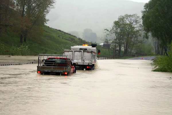 Trucks cross a flooded Tauwhareparae Road after torrential rain across the Poverty Bay area (NZPA)