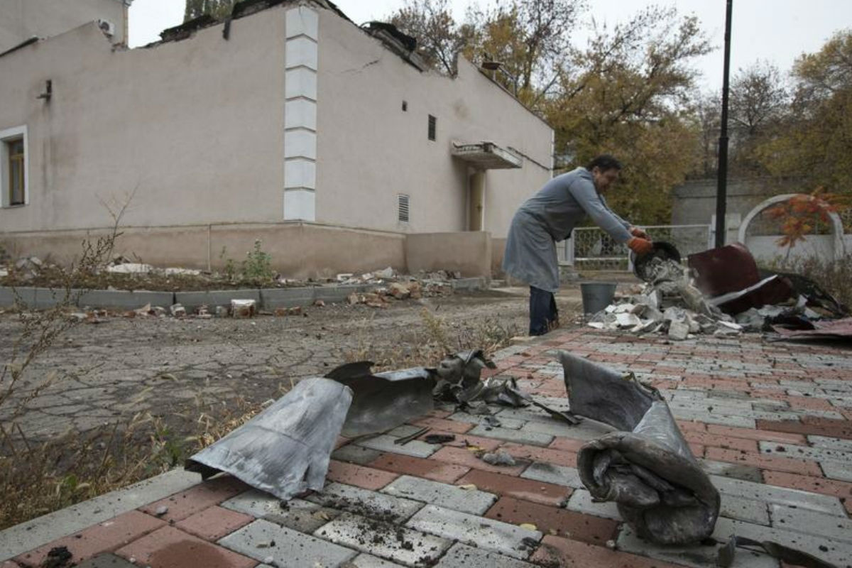 Remains of missiles are seen as a man cleans debris after recent shelling in a yard of hospital in Donetsk (Reuters)