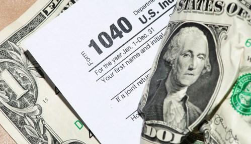 dollar bills with a 1040 tax form beside them