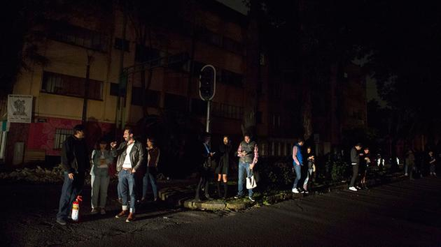 People who evacuated from bars during an earthquake stand in the street in Mexico City, sections of which lost power, just before midnight on Thursday, Sept. 7, 2017.