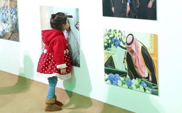 طفلة تطبع قبلة على صورة للملك سلمان في عفوية تامة
