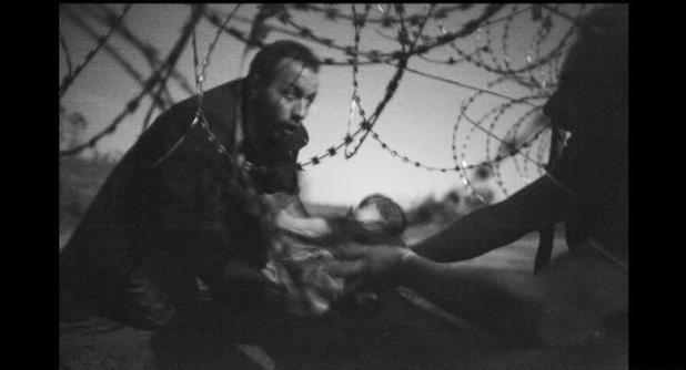 رجل على الحدود المجرية - الصربية يحمل طفلاً في الساعة الثالثة صباحاً ويمرره من تحت الأسلاك الحدودية الشائكة