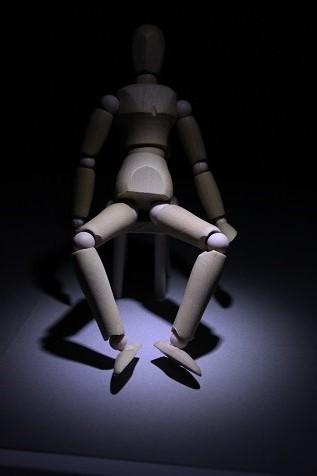 慢性腰痛で座り込んだデッサン人形正面