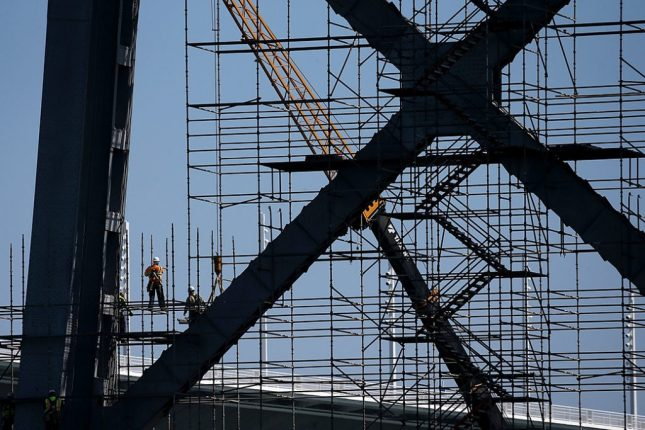 Workers construct scaffolding on a bridge in California, March 2014.