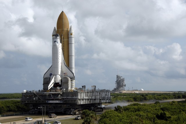 Under troubled skies, <em>Atlantis</em> makes its way out to the pad atop one of the Crawler-Transporters to embark on STS-129.
