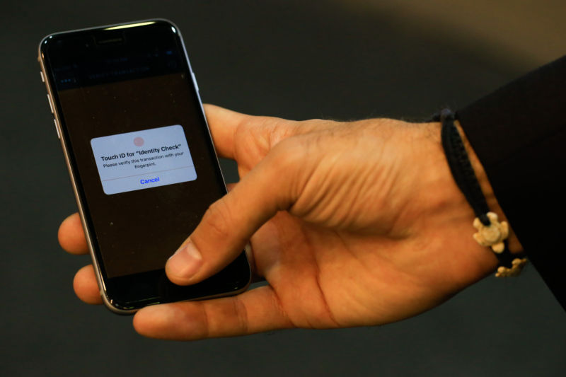 An employee demonstrates fingerprint security software on a smartphone at the MasterCard Inc. stand at the Mobile World Congress in this arranged photograph in Barcelona, Spain, on Wednesday, February 24, 2016.
