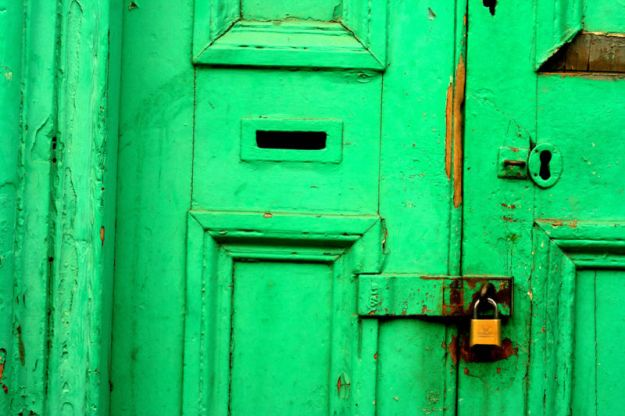 A green exterior door is sealed with a padlock.