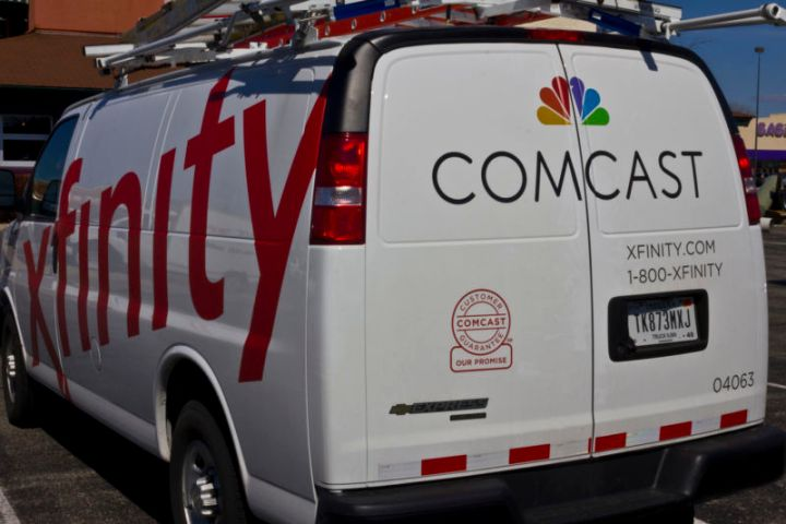 A Comcast service van covered in logos.
