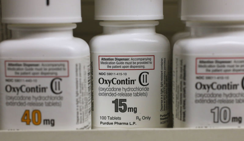 Consumer-sized bottles of prescription drugs sit on a shelf.