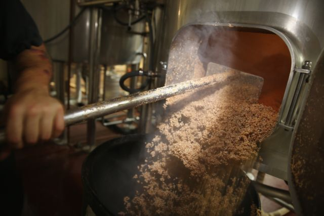 No barley, no beer: A beer brewer pulls malted barley from the mash tun at Wynwood Brewing Company in Miami, Florida.