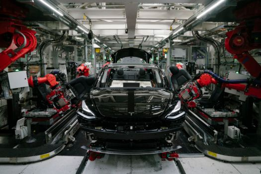 Robotic arms install the front seats to a Model 3 at the Tesla factory in Fremont, California.