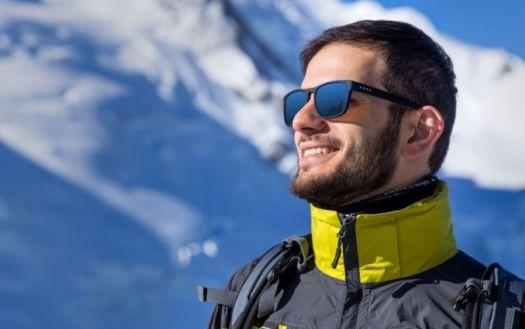 Dude enjoying winter sports in sunglasses is happy.