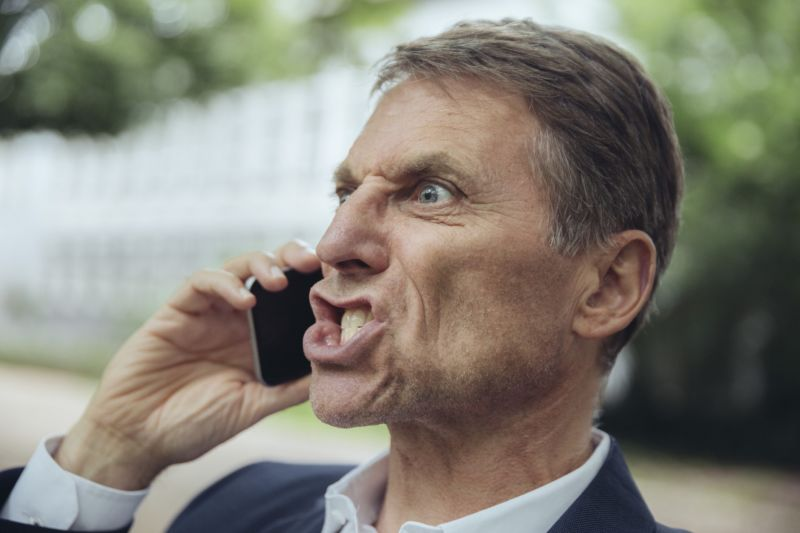 An angry man yelling into a cell phone.