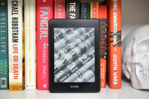 The 2018 Kindle Paperwhite leaning against a shelf of books.