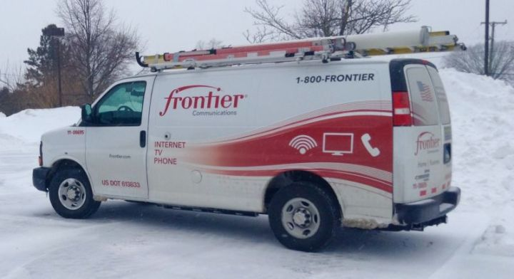 A Frontier Communications service van parked in a snowy area.