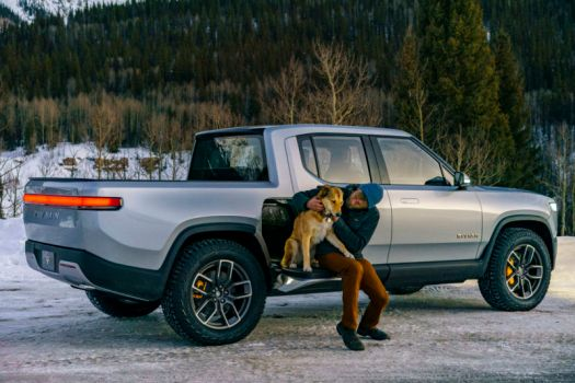 A man and a dog sit on an electric pickup truck