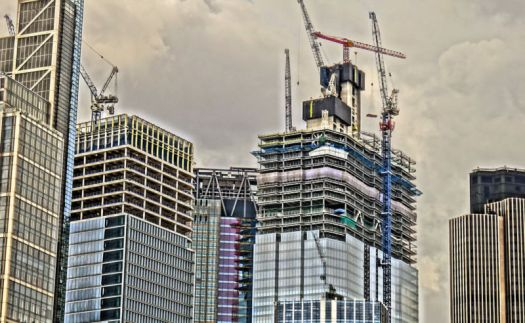 Stylized image of glass skyscrapers under construction.