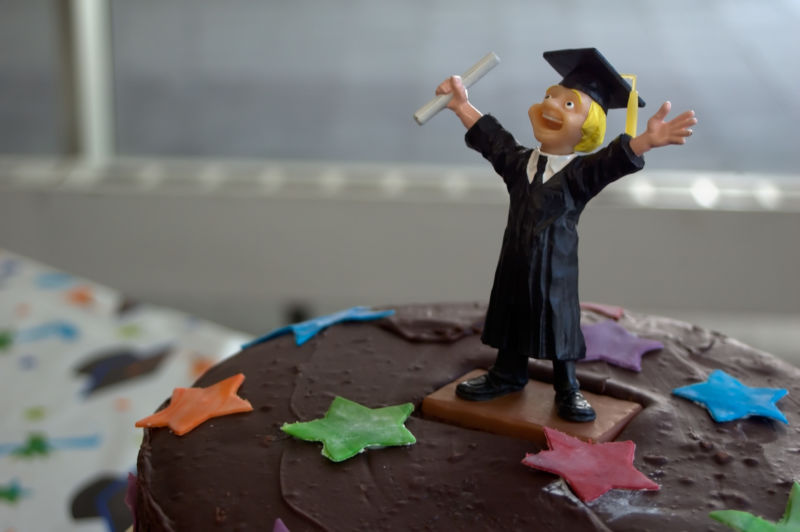 A chocolate cake is decorated by the plastic figurine of a celebratory graduate, complete with diploma and mortarboard.