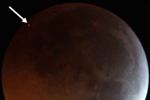 The flash from the impact of a meteoroid on the eclipsed Moon in early 2019, seen as the dot at top left.