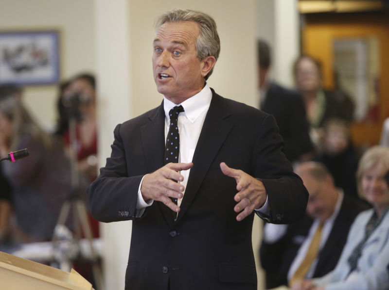 A man in a suit addresses a small crowd.
