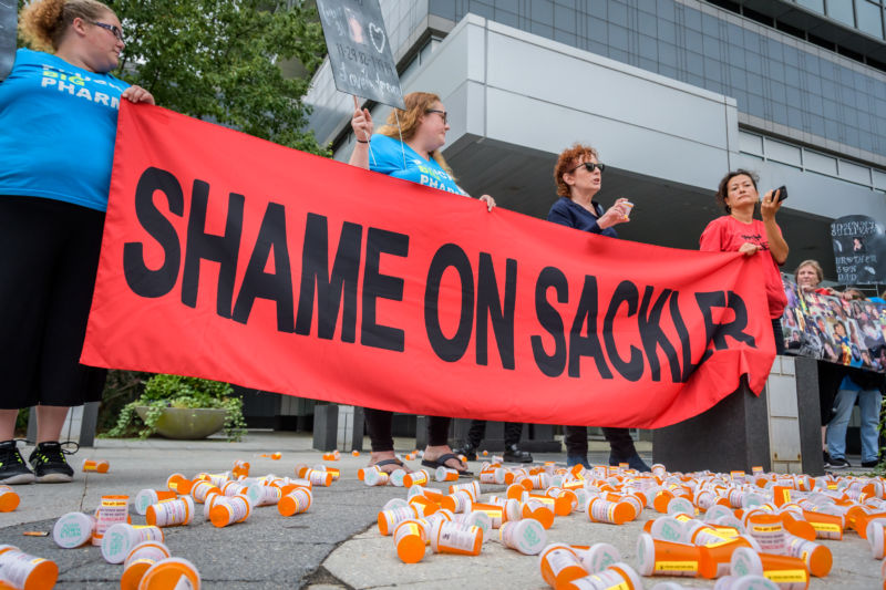 Protestors hold up a banner while surrounded by empty prescription bottles.