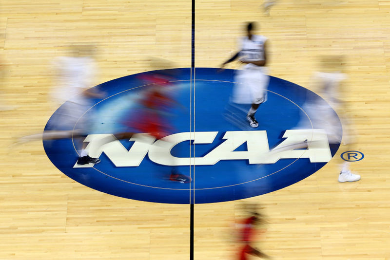 College basketball players running on top of the NCAA logo on a basketball court.