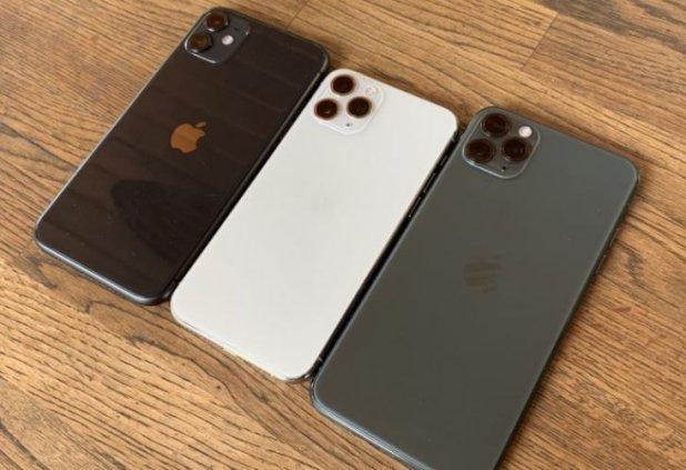 iPhone: Multiple smartphones on table.
