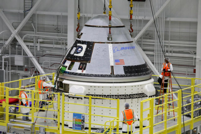 The crew module of Boeing's CST-100 Starliner spacecraft is lifted onto its service module on October 16 inside the Commercial Crew and Cargo Processing Facility at Kennedy Space Center in Florida.