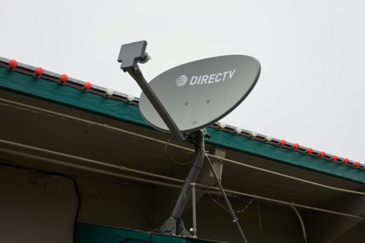A DirecTV satellite dish mounted to the outside of a building.