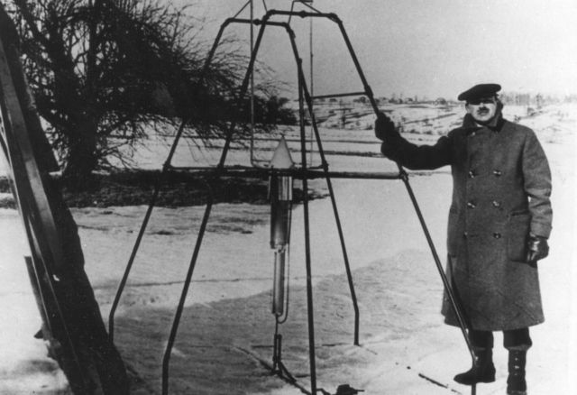 Robert H. Goddard, bundled against the cold weather of March 16, 1926, holds the launching frame of his most notable invention — the first liquid-fueled rocket, an example of a