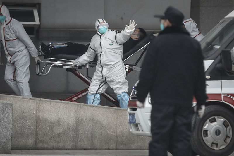 A person in full, white protective suit, blue face mask, and goggles, helps wheel a patient on a gurney into a hospital. His hand is outstretched as if he is signaling someone not to come near.