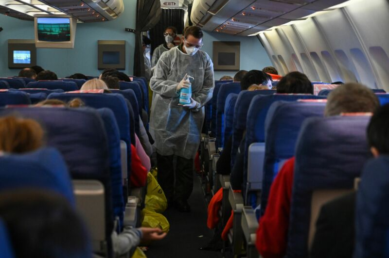 A crew member of an evacuation flight of French citizens from Wuhan gives passengers disinfectant during the flight to France on February 1, 2020, as they are repatriated from the coronavirus hot zone.