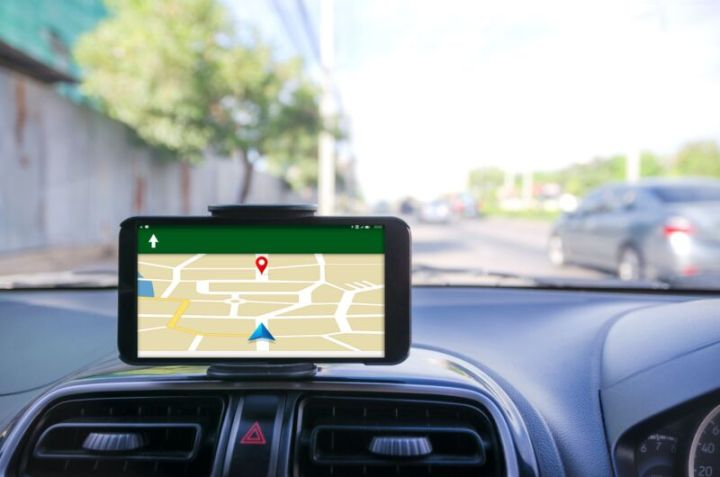 A cell phone displays a map and directions while mounted on a car dashboard.