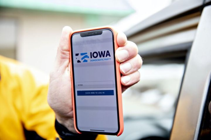 A man's hand holding an iPhone displaying the Iowa Democratic Party's app for reporting caucus results.