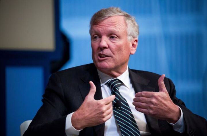 Charter CEO Tom Rutledge gesturing with his hands and speaking at a conference.