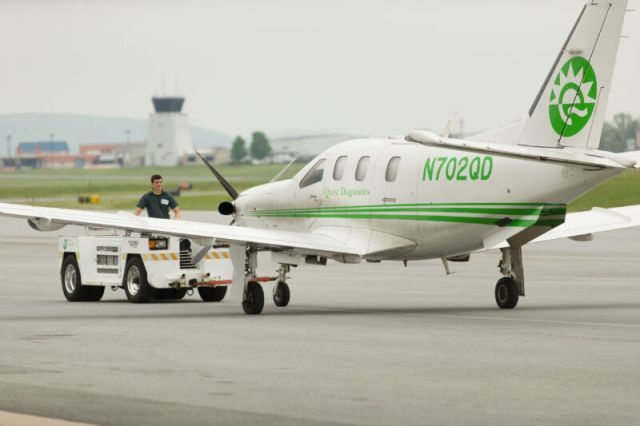 A white and green airplane belonging to Quest Diagnostics is on the ground at Reading Regional Airport