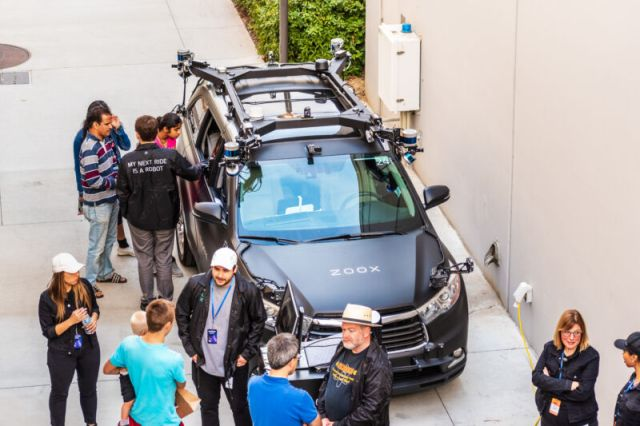People examine a Zoox test vehicle in 2019. The company has yet to show off the custom-designed vehicle it plans to use for its commercial service.