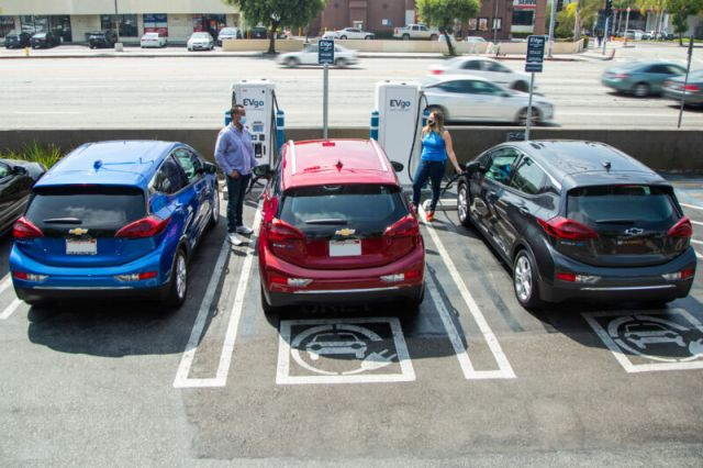 Two masked, socially distanced people charge their electric cars.