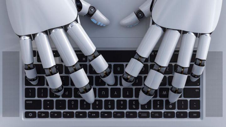 Robot hands work a laptop keyboard.