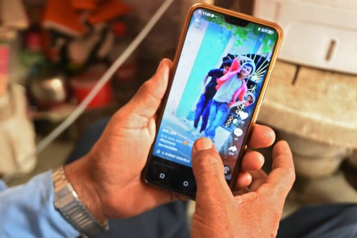 A person's hands holding a smartphone with the app TikTok displayed on the screen.