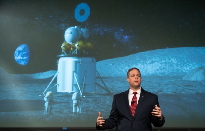 A man in a suit speaks in front of a mural of the Moon landing.
