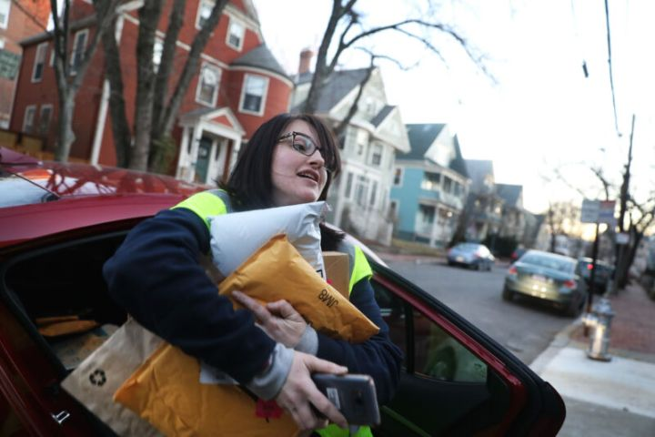 An Amazon Flex driver delivers an armload of packages in Cambridge, Mass., on Dec. 18, 2018.