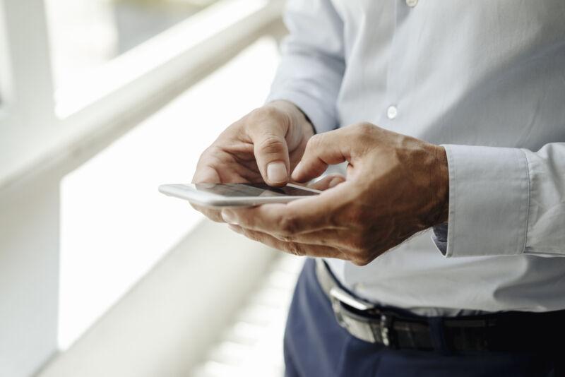 Stock photo of man using smartphone.