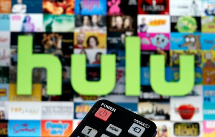 Photo illustration of a remote control in front of a television screen displaying Hulu TV content.
