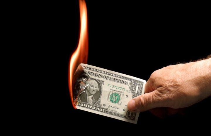 A one-dollar bill set on fire.
