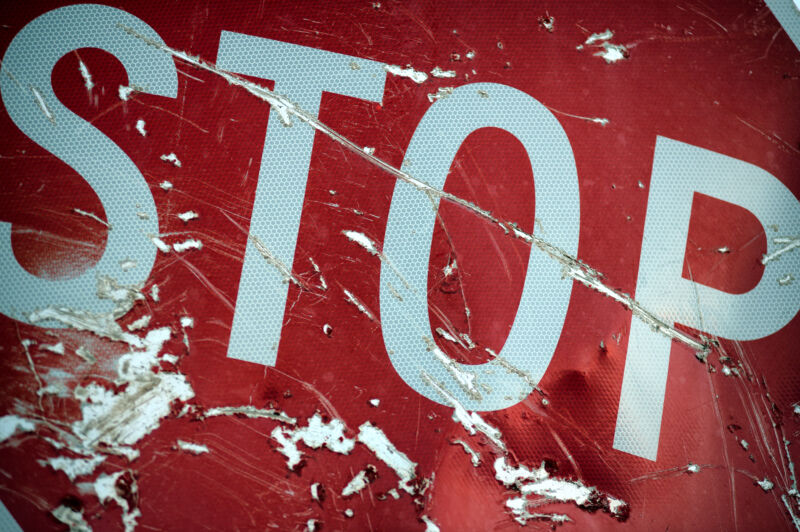 Close-up of a red stop sign after a traffic accident. The sign is heavily scratched and dented. Many vehicle accidents are attributed to drunk driving in Hawaii. Unfortunately many end up as fatalities.